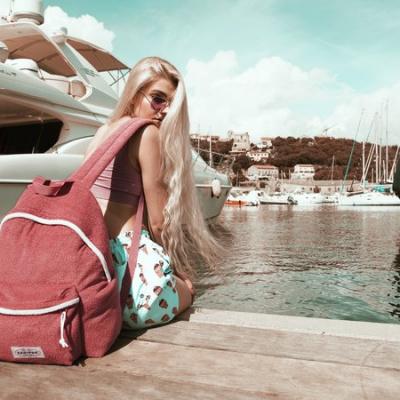 blond pige med coralfarvet eastpak taske på