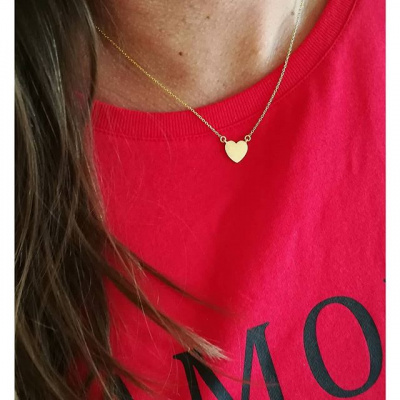 kvinde med rød t-short og fin lille guldhalskæde med hjerte
