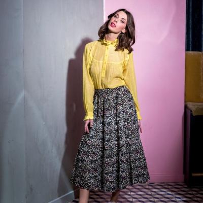 Lollys Laundry, kvinde i gul skjorte og grå nederdel