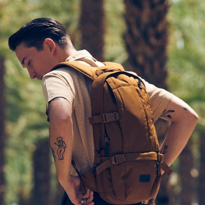 und mand med brun eastpak rygsæk i skov