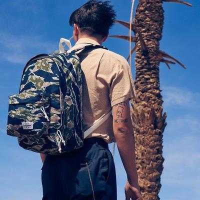 ung mand med eastpak rygsæk i skov