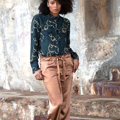 kvinde i brune bukser og grøn skjorte